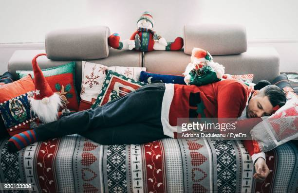 Mid Adult Man In Santa Costume Sleeping On Bed