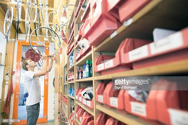 mid adult man in storage room choosing bicycle wheel - sigrid gombert stock pictures, royalty-free photos & images