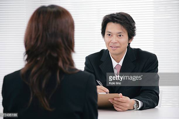 A mid adult man interviewing a young woman