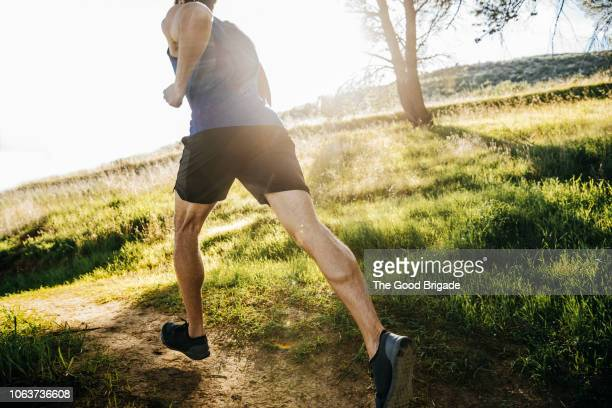 mid adult man jogging in park on sunny day - jogging stock pictures, royalty-free photos & images