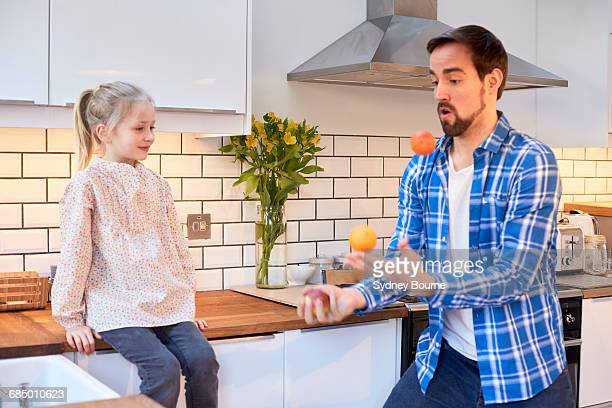 Mid adult man juggling fruit for daughter in kitchen