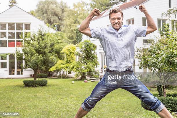Mid adult man jumping for joy in front of house