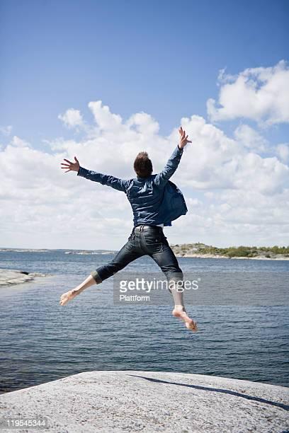 Mid adult man jumping on coastline
