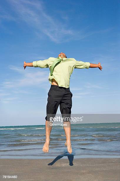 mid adult man jumping on the beach with his arms outstretched - rolled up trousers stock pictures, royalty-free photos & images