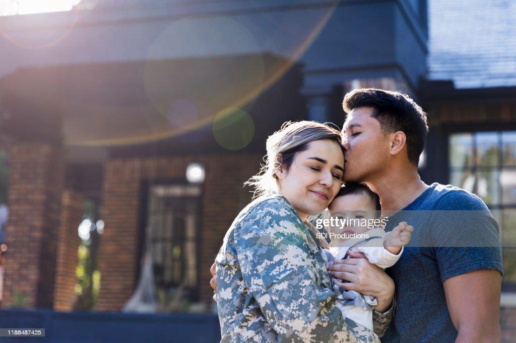 Mid adult man kisses his soldier wife : Stock Photo