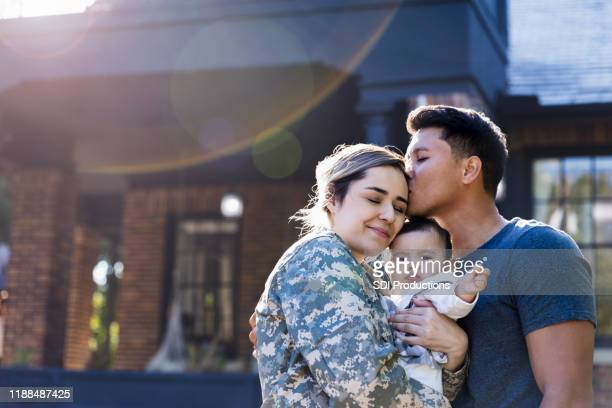 mid adult man kisses his soldier wife - army soldier stock pictures, royalty-free photos & images