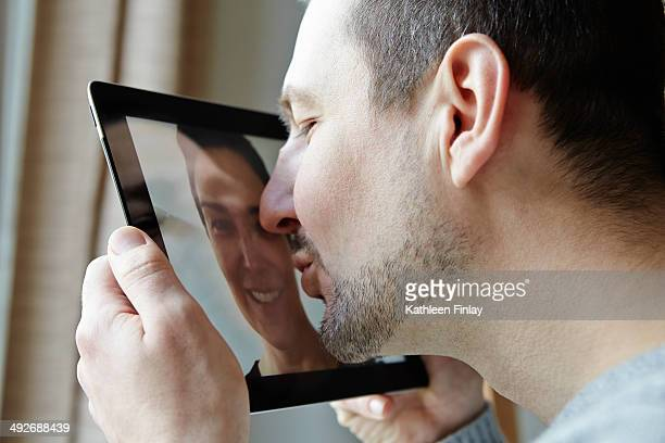 Mid adult man kissing screen of digital tablet