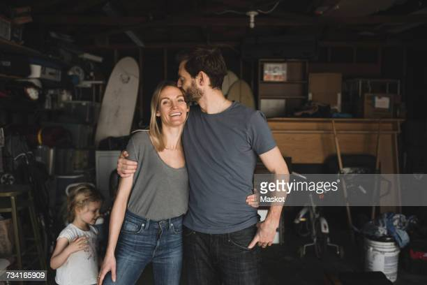 Mid adult man kissing woman by daughter in storage room of house