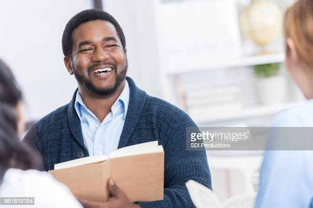Mid adult man laughs during book club discussion