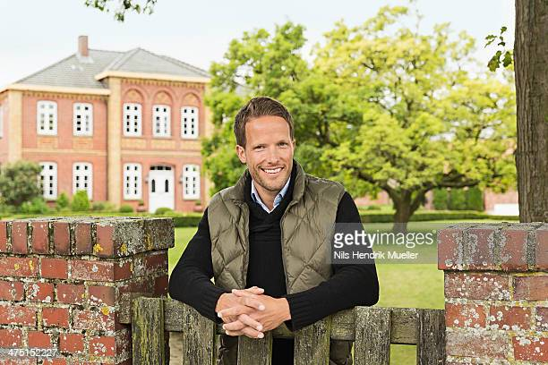 Mid adult man leaning on wooden gate