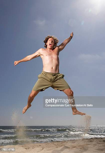 Mid adult man leaping on beach