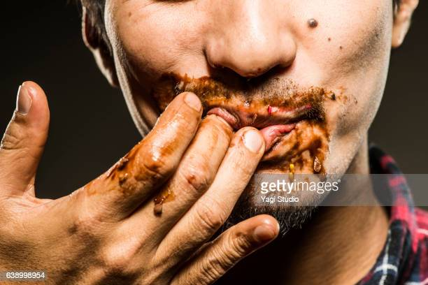 mid adult man licking chocolate,close up shot - gier stock-fotos und bilder