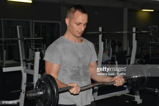 Mid Adult Man Lifting Weights In Gym