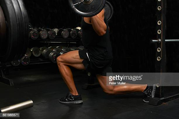 Mid adult man, lifting weights, low section
