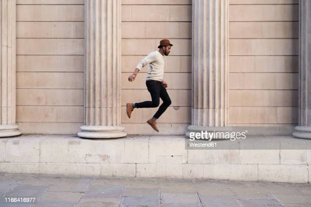 mid adult man listening music and jumping - in de lucht zwevend stockfoto's en -beelden