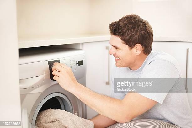 Hombre de mediana edad ropa de carga de la máquina de lavado