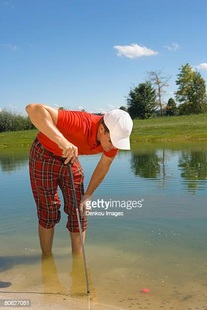 mid adult man looking at a golf ball trapped in waterhole - バンカー ストックフォトと画像