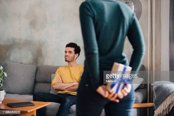mid adult man looking at girlfriend hiding gift box while standing in living room - hands behind back stock pictures, royalty-free photos & images