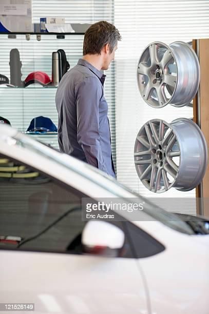 Mid adult man looking at hubcap in car showroom
