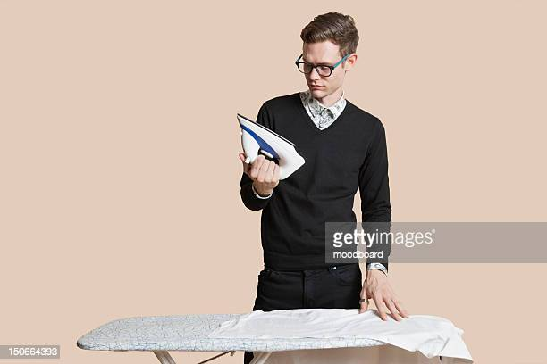 Mid adult man looking at iron over colored background