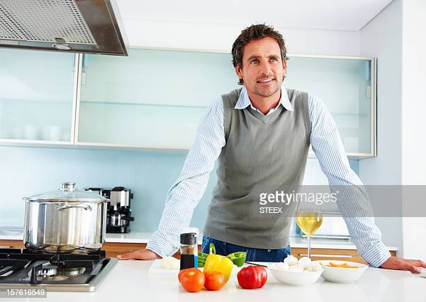 Mid adult man looking away while standing in kitchen