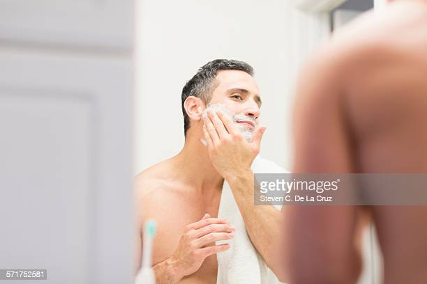 Mid adult man, looking in mirror, applying shaving foam to face, rear view