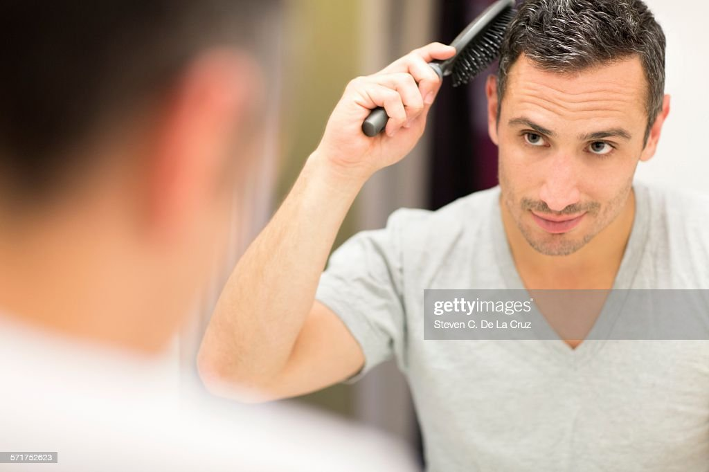Mid adult man, looking in mirror, brushing hair : Stock Photo