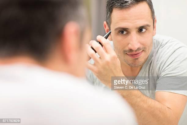 Mid adult man, looking in mirror, using tweezers