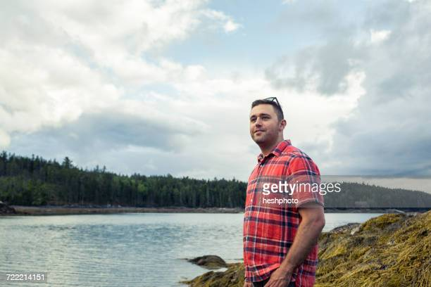 mid adult man looking out at coast of maine, usa - heshphoto stock-fotos und bilder