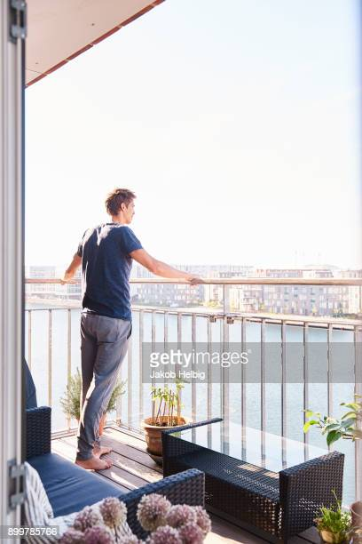 Mid adult man looking out from waterfront apartment balcony