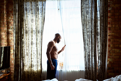 Mid adult man looking out of window in hotel room - gettyimageskorea
