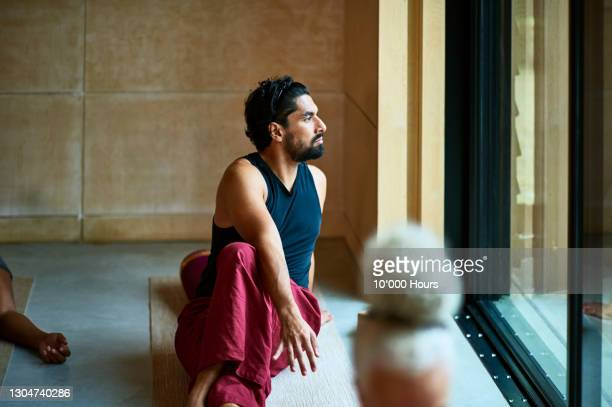 mid adult man looking through window in yoga studio - one mid adult man only stock pictures, royalty-free photos & images
