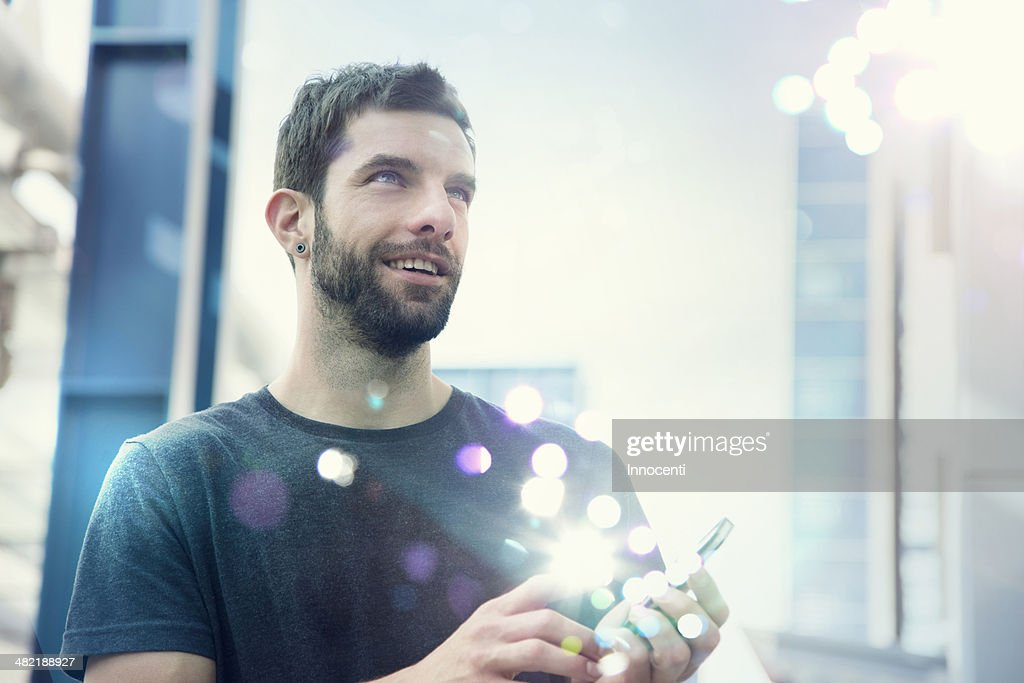 Mid adult man looking up at lights coming from smartphone : Stock Photo