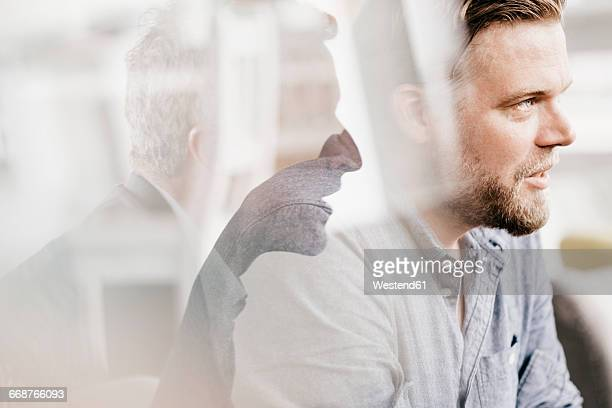 Mid adult man looking worried, second man giving advice