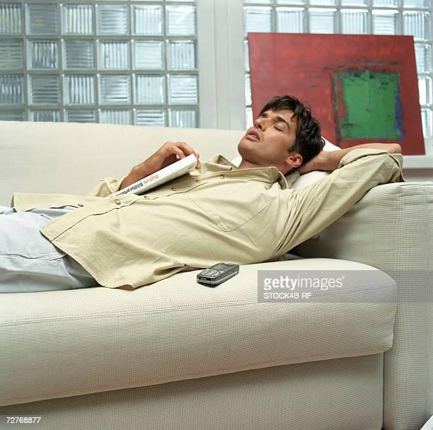 Mid adult man lying on a settee with a handbook, sleeping