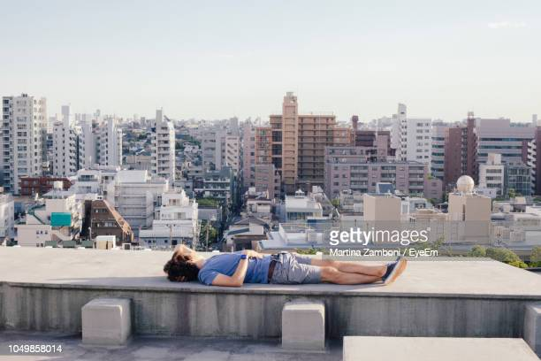mid adult man lying on building terrace against sky - 屋根 ストックフォトと画像