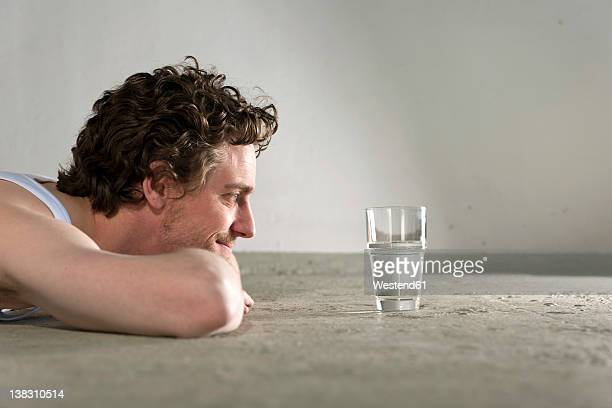 Mid adult man lying on floor and staring at glass of water