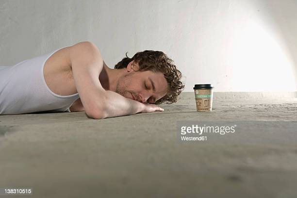 mid adult man lying on floor with coffee cup beside - human body part stock pictures, royalty-free photos & images