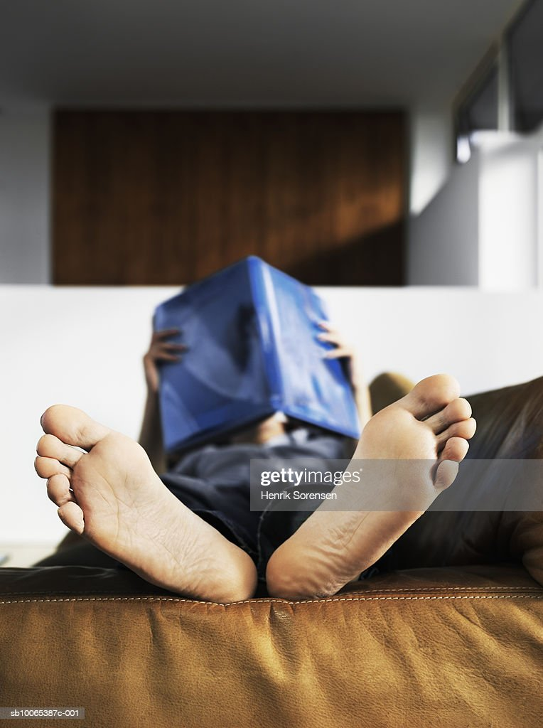 Mid adult man lying on sofa reading book, focus on barefoot : Foto stock
