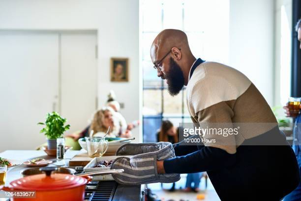 mid adult man making dinner wearing oven gloves - evening meal stock pictures, royalty-free photos & images