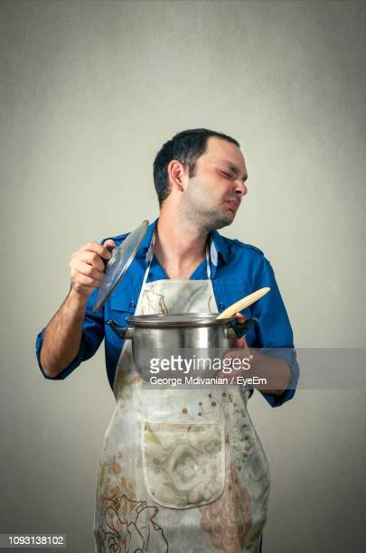 mid adult man making face while holding open cooking pot against gray background - failure stock pictures, royalty-free photos & images