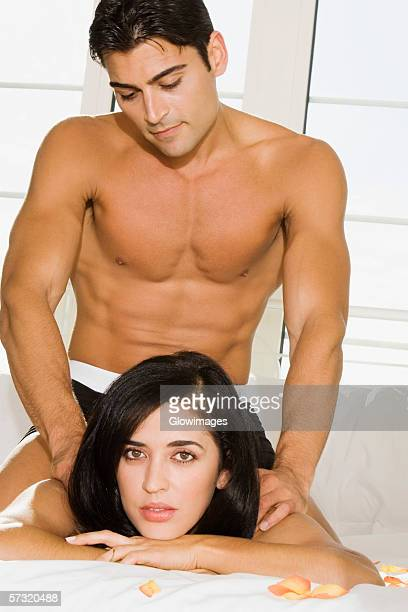 Mid adult man massaging a mid adult woman's shoulders on the bed