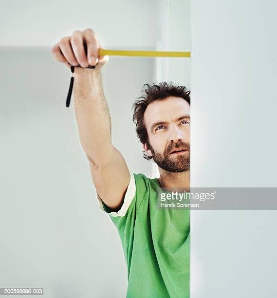 Mid adult man measuring new flat with measuring tape