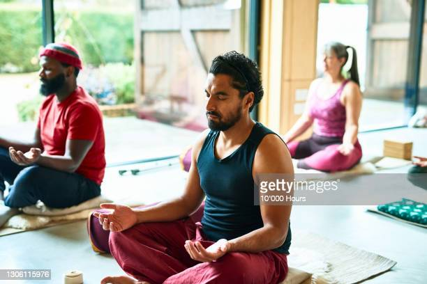 mid adult man meditating in yoga class - sitting stock pictures, royalty-free photos & images