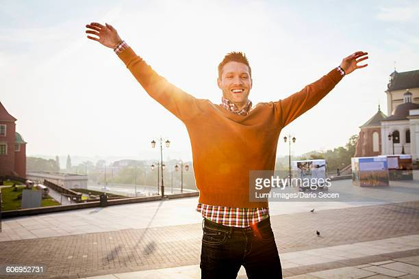 Mid adult man on a city break standing with arms raised
