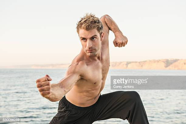 Mid adult man on beach in kung fu pose