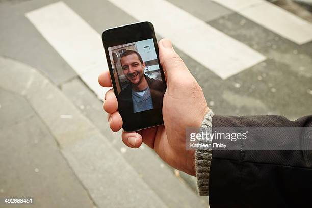 mid adult man on sidewalk holding smartphone with photograph on screen - one man only stock pictures, royalty-free photos & images