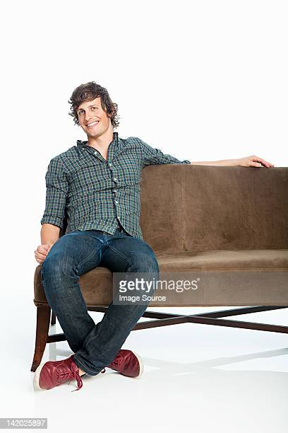 Mid adult man on sofa against white background