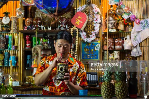 mid adult man or bartender sipping a drink in a tropical themed drinking establishment - bar drink establishment stock pictures, royalty-free photos & images