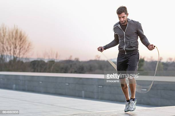 Mid adult man, outdoors, skipping with skipping rope